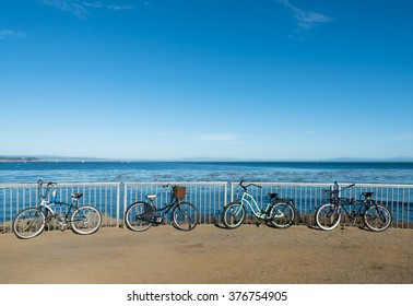 Bikes neatly arranged and chained to the fence on Santa Cruz boardwalk
