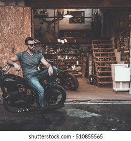 Bikes are not for everyone. Handsome young man sitting on his bike with motorcycle garage in the background