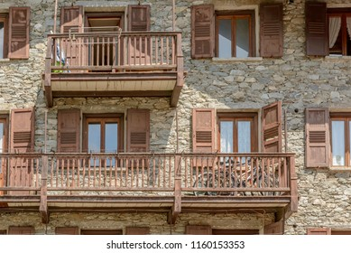 bikes parked on wooden balcony of traditonal stone house, shot on a bright summer day at Gressoney Saint Jean,  Lys valley, Aosta, Italy