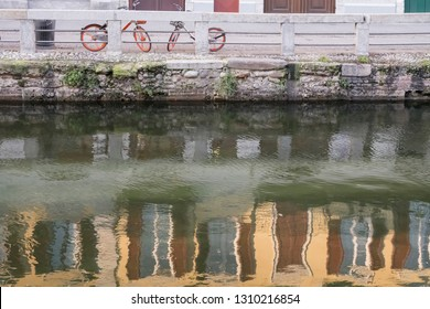bikes stand on enbankment in front of Naviglio canal water with  blurred reflections of old facades in it ,  shot in bright winter light at Milan, Lombardy,  Italy