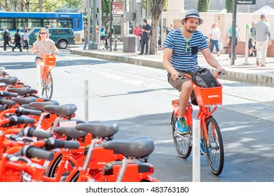 Biketown riders pass by a station accross Pionner Square on SW Morrison ST. Portland, OR, 9/12/2016