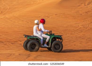 Biking Dubai Adventure Tour – Young copule of tourists having fun on Bike Riding in dunes of Dubai