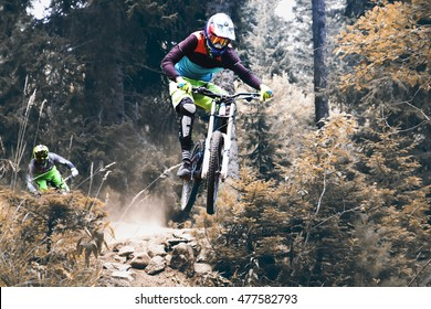 Biking as extreme and fun sport. Biker high jumping downhill on the mountain.