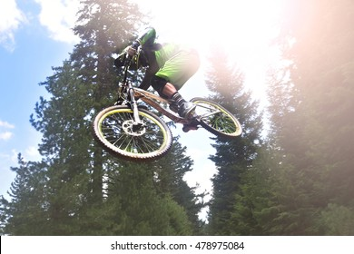 Biking as extreme and fun sport. Cyclist high jumping downhill on the mountain.