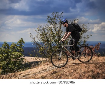 Biking in the Franconian Hills in Northern Bavaria. Caucasian Young man in black sports outfit with his Trekking bike on a rock, looking into the distance. Shot in High Summer August on an afternoon