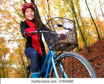 Biking, Woman on bike in autumn forest. Beautiful mixed asian / caucasian model.