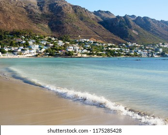 Bikini Beach in Gordon's Bay, in False Bay South Africa. A Blue Flag beach. A beautiful beach in a bay,  surrounded by mountains. A calm sea on a sunny day with blue sky