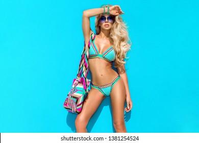 Bikini fashion. Beautiful sexy tanned woman in elegant colorful bikini and sunglasses is posing on the Caribbean beach.  Beachwear. Summertime. Hot bikini model.