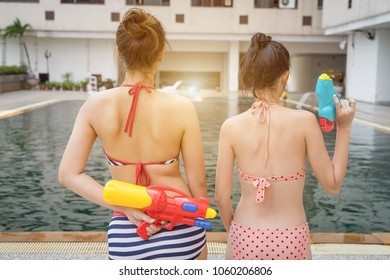 Bikini girl holding water gun at swimming poolFestival celebrate national culture party in Thailand tradition New year.Young Asian woman at Songkran festival.