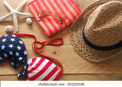 bikini is striped american flag, brown hat and sunglasses put on red striped towel with shells and starfish are placed on a wooden background