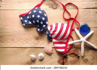 bikini is striped american flag and sunglasses with shells and starfish are placed on a wooden background
