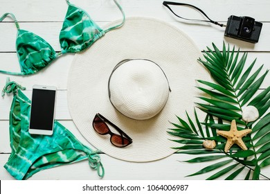 Bikini suit, hat, sunglasses, film camera, smartphone, sea star, green plam leaves arranged on wooden baclground. Summer holidays vacation concept.
