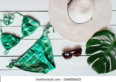 Bikini suit, hat, sunglasses, sea star, green plam leaf arranged on wooden baclground. Summer holidays vacation concept. Tropical poster banner, postcard.