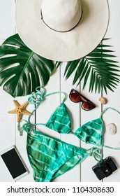 Bikini suit, hat, sunglasses, smartphone, sea star, green plam leaves arranged on wooden baclground. Summer holidays vacation concept. Vertical tropical poster banner, postcard.