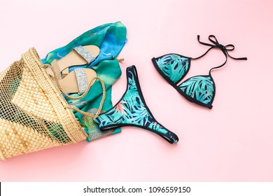 Bikini swimsuit with tropical print, silver glitter flat sandans, wicker beach bag, sarong on pink background. Overhead view of woman's swimwear and beach accessories.