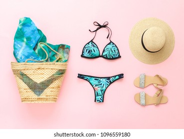 Bikini swimsuit with tropical print, silver glitter flat sandans, straw hat, wicker beach bag, sarong on pink background. Overhead view of woman's swimwear and beach accessories. Flat lay, top view.