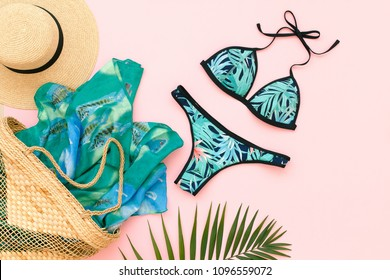 Bikini swimsuit with tropical print, straw hat, wicker beach bag, sarong and tropical date palm leaves on pink background. Overhead view of woman's swimwear and beach accessories. Flat lay, top view.