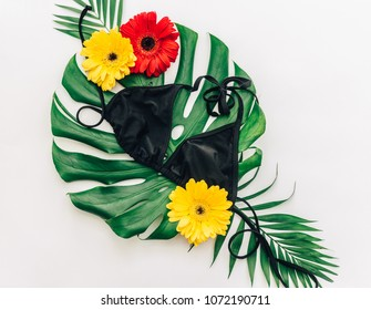 Bikini and Tropical leaves with flowers. Summer concept. Flat lay trendy background. Top view