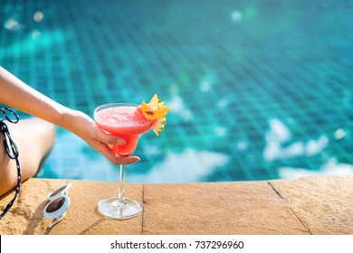 Bikini woman in pool relaxing with watermelon juice sunglasses, young asian beautiful sexy female resting in vacation on summer season with hat at resort swimming pool