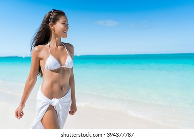 Bikini woman relaxing in white sun protection beachwear walking on tropical Caribbean beach with turquoise ocean water during summer vacations. Happy lifestyle Asian girl.