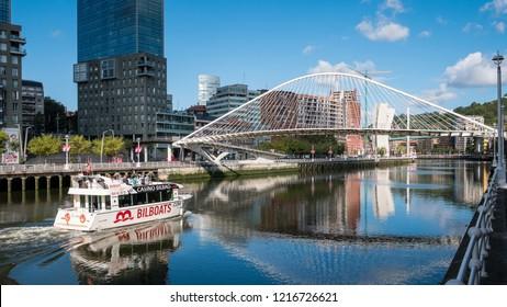 Bilbao, Basque Country, Spain - September 1 2017: a tourist boat heads along the estuary towards the Zubizuri Bridge in the City of Bilbao