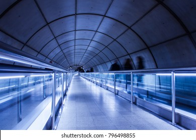 Bilbao, Bizkaia, Spain - Nov 9, 2017: Tunnel in Bilbao metro station with long aisle and mechanical transportation platforms. Futuristic blue color effect