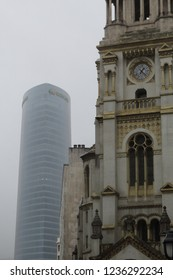 Bilbao, Spain - December 08, 2017: The modern Iberdrola Tower (Torre Iberdrola) skycraper in Bilbao, Basque Country, Spain, next to an ancient Catholic church in a foggy cold winter day