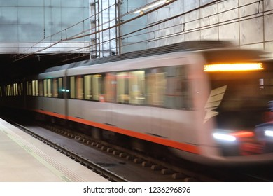 Bilbao, Spain - December 08, 2017: A motion blur photo of the Bilbao metro on rails getting to the Guggenheim Museum stop during an autumn cloudy day, in Basque Country, Spain