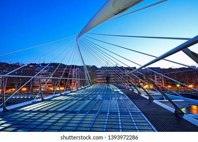 BILBAO, SPAIN, DECEMBER 14TH 2012; The pedestrian Zubizuri footbridge illuminated in Bilbao at sunrise, designed by Santiago Calatrava