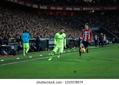 BILBAO, SPAIN - FEBRUARY 10, 2019: Lionel Messi (L) and Markel Susaeta (R) dispute the ball during a Spanish League match between Athletic Club Bilbao and FC Barcelona at San Mames Stadium