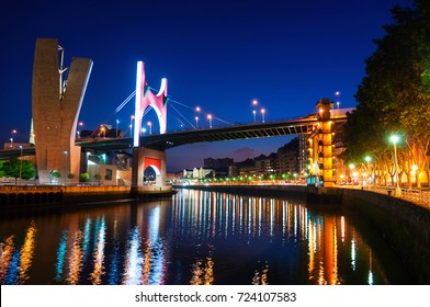 Bilbao, Spain. Illuminated Salbeko zubia Bridge over Nevion River in Bilbao, Spain at night. Lights reflection in the water, buildings at the background and clear dark blue sky