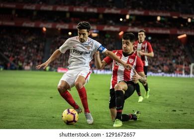 BILBAO, SPAIN - JANUARY 13, 2019: Jesus Navas (L) and Yuri Berchiche (R) dispute the ball during a Spanish League match between Athletic Club Bilbao and Sevilla FC at San Mames Stadium