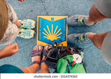 "Bilbao, Spain - July 11, 2017:  Three pairs piligrims feet on the start of the Camino de Santiago or ""The Way of Saint James "" famous rout in Bilbao, Spain"