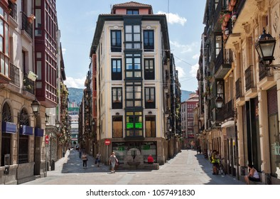 Bilbao, Spain - July 29, 2013: the old centre of Bilbao (barrio viejo), a pedestrian shopping zone with only a few people walking the sunlit streets because of siesta,