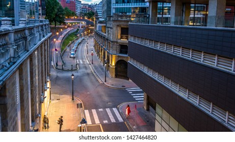 Bilbao, Spain - May 06, 2019 - A woman in a white dress and red coat crossing Uribitarte Street at sunset in the city center of Bilbao. Bilbao is a city in northern Spain.