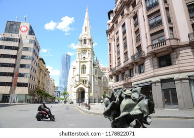 Bilbao, Spain - May 21st 2014: Old Church Corner on Urban Street, motorcyclist on road with Metal Sculture Art in Foreground.