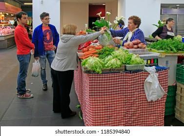 Bilbao, Spain - May 27, 2018: woman sells vegetables in Bilbao Spain