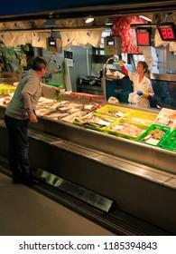 Bilbao, Spain - May 27, 2018: woman sells fish and sea food at the market in Bilbao, Spain