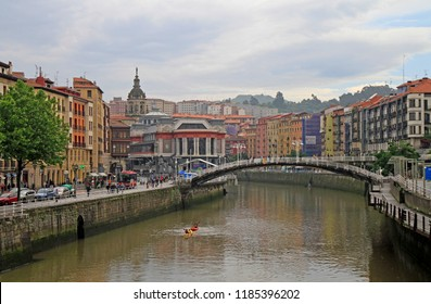 Bilbao, Spain - May 27, 2018: people walk by embankment of river Nervion in spanish city Bilbao