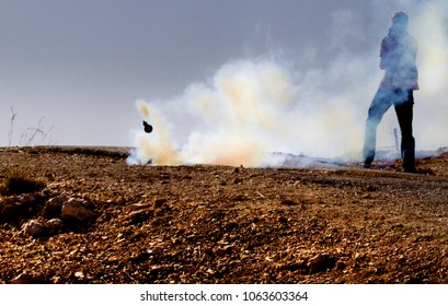 Bilin, Palestine, December 3, 2010: Protester escapes tear gas grenade by a security fence during weekly demonstrations against Palestinian land confiscation and building Jewish settlement in Bilin.