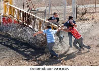 Bilin, Palestine, December 3, 2010: Protesters are moving gate of security fence in during weekly demonstrations against Palestinian land confiscation and building Jewish settlement in Bilin.