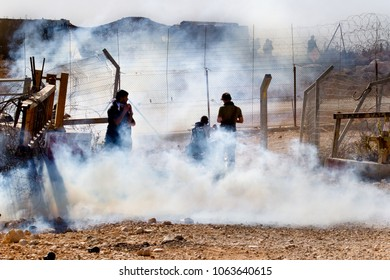 Bilin, Palestine, December 3, 2010: Protesters by a security fence in a cloud of tear gas during weekly demonstrations against Palestinian land confiscation and building Jewish settlement in Bilin.
