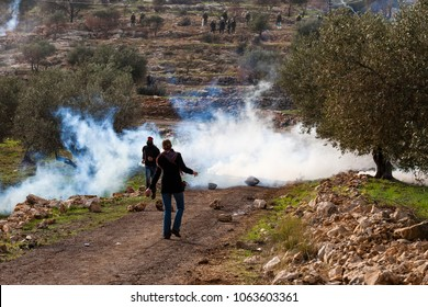 Bilin, Palestine, December 31, 2010: Protesters are facing IDF squad shooting tear gas during weekly demonstrations against Palestinian land confiscation and building Jewish settlement in Bilin.