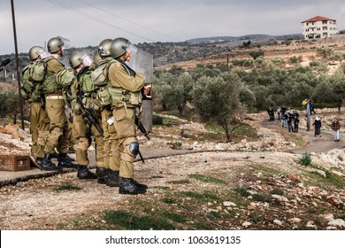 Bilin, Palestine, December 31, 2010: Israel Defence Force squad faces protester during weekly demonstrations against Palestinian land confiscation and building Jewish settlement in Bilin.