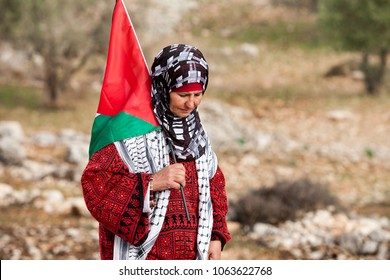 Bilin, Palestine, December 31, 2010: Palestinian woman walks with Palestinian flag during weekly demonstrations against Palestinian land confiscation and building Jewish settlement in Bilin.