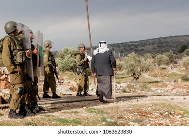 Bilin, Palestine, December 31, 2010: Elderly Palestinian man is walking in front of Israel Defence Force soldiers during weekly demonstrations against Palestinian land confiscation.