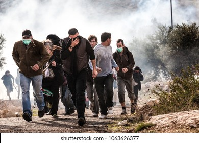 Bilin, Palestine, December 31, 2010: Palestinian protesters escape the tear gas during weekly demonstrations against Palestinian land confiscation and building Jewish settlement in Bilin.