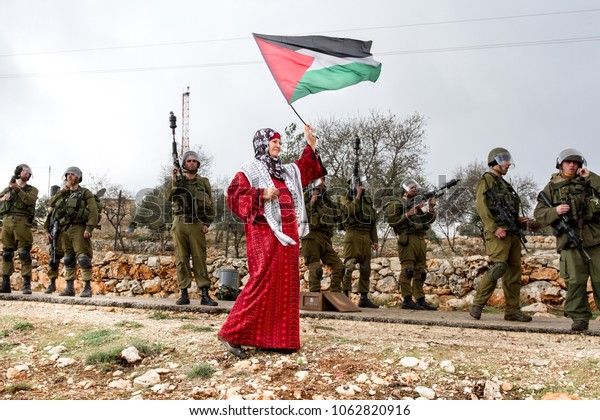 Bilin, Palestine, December 31, 2010: Palestinian woman walks with Palestinian flag in front of Israel Defence Force soldiers during weekly demonstrations against Palestinian land confiscation in Bilin