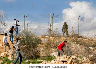 Bilin, Palestine, January 1, 2011: Palestinian youth throws stones at Israeli soldier in Bilin during demonstration against Israeli presence in West Bank.