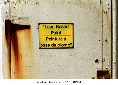 Bi-lingual sign warning of lead based paint on an old rusty door